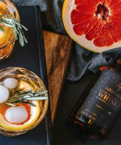 Barrel Aged Whiskey Maple Syrup pictured with two whisky cocktails